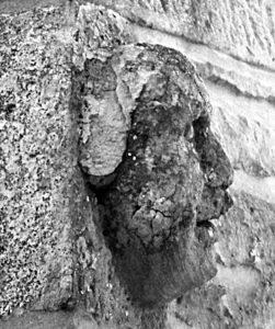 Una testa scolpita incastonata in un angolo di abitazione a Chiesina Farnè