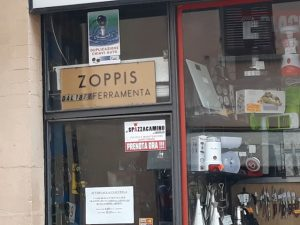 L'adesivo degli Spazzacamino di Manlio nella vetrina della Ferramenta Zoppis