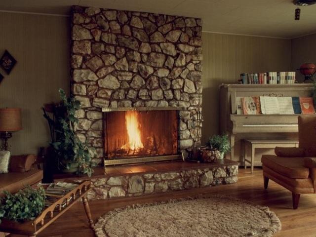 Rivestimento del camino in pietra con sassi in soggiorno e pavimento in legno