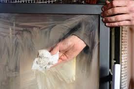 Puliza del vetro di una stufa con carta e cenere