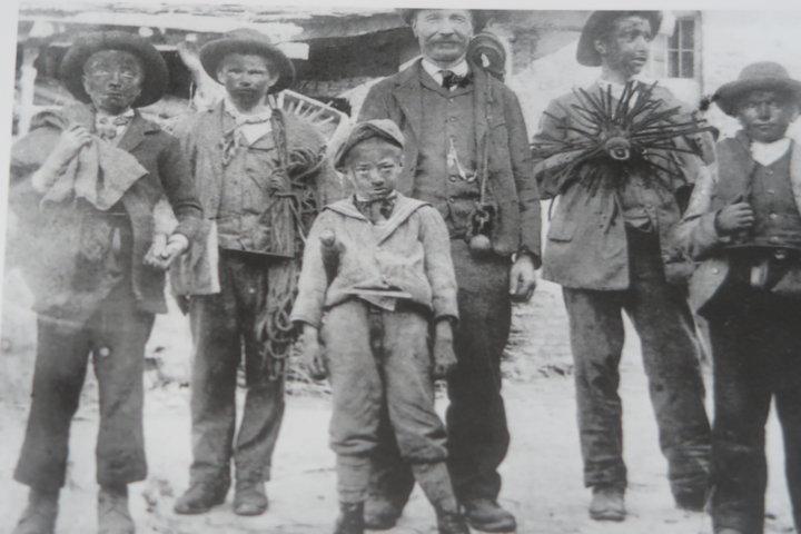 Un'immagine storica di bambini che fanno il lavoro dello spazzacamino